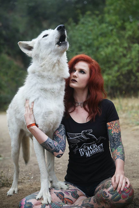 A commercial photography portrait of a woman beside a white wolf like dog posed outdoors - commercial photography tips
