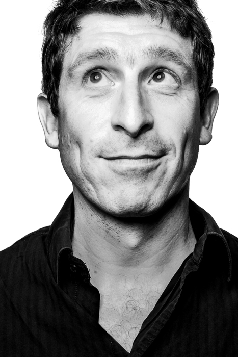 Black and white portrait of a man looking to the upper corner of the frame, making a funny face