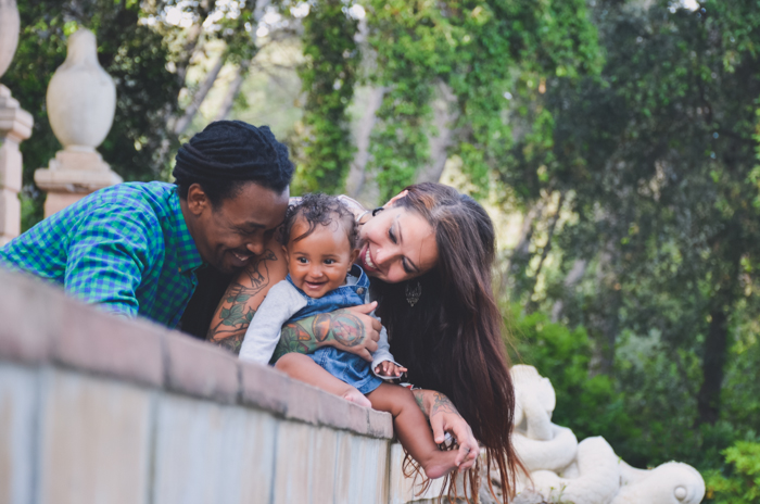 Family portrait photo of a couple and small baby leaning on a wall