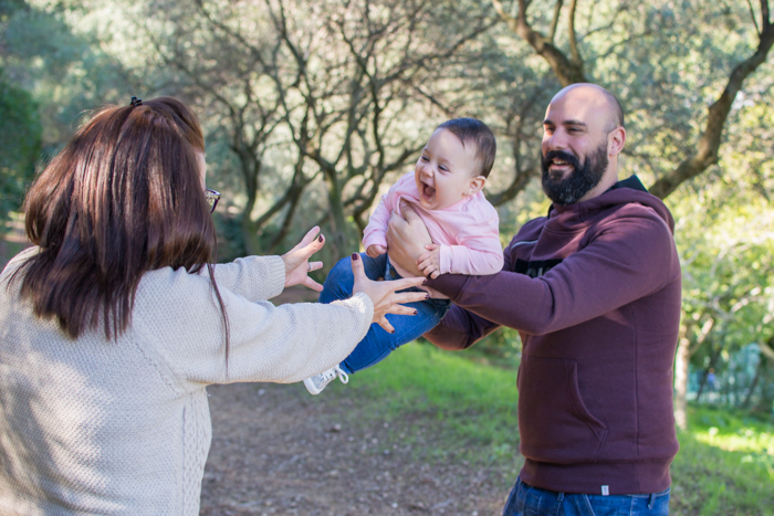 Family portrait photo of a couple playfully passing their baby