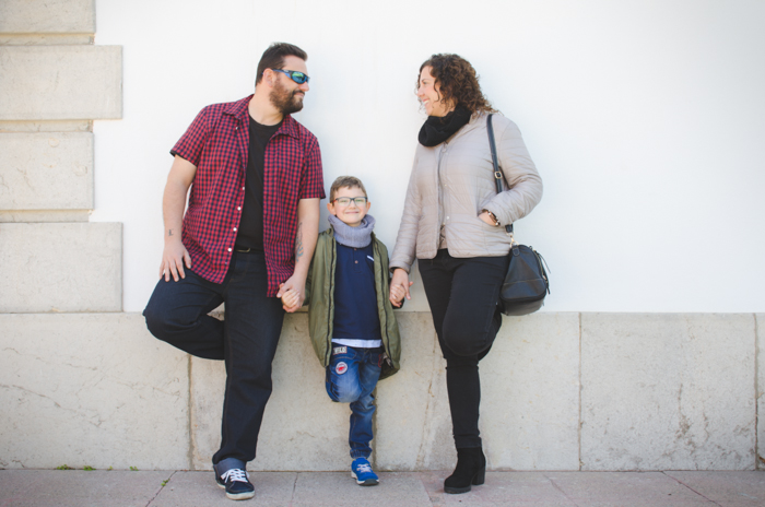 Family portrait photo of a couple and son leaning against a wall