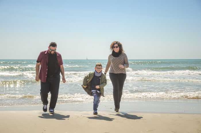 Family portrait photo of a couple and son walking on a beach