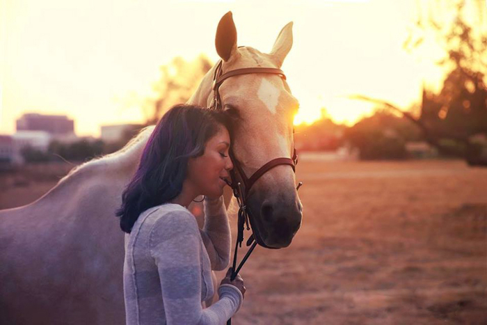 A sweet horse photography portrait of a girl pressing her forehead against a light brown horse at evening time