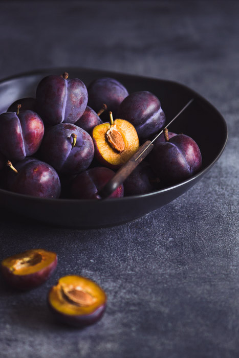 Still life photography of a bowl of plums ion dark background shot with a 105mm on a full frame. 10 Tips for Shooting with Macro Lenses in Still Life Photography.