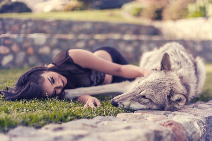 Sweet and dreamy portrait of a girl and dog lying on the grass