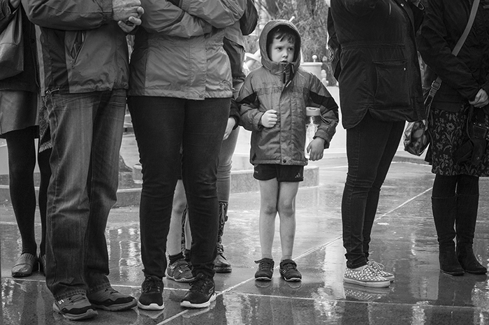 Black and white street photography of a little boy in the centre of group of adults in the rain. Street photography tips