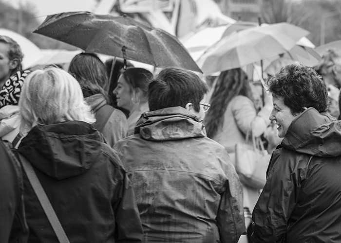 Black and white street photography of a group of adults in the rain. Rain photography