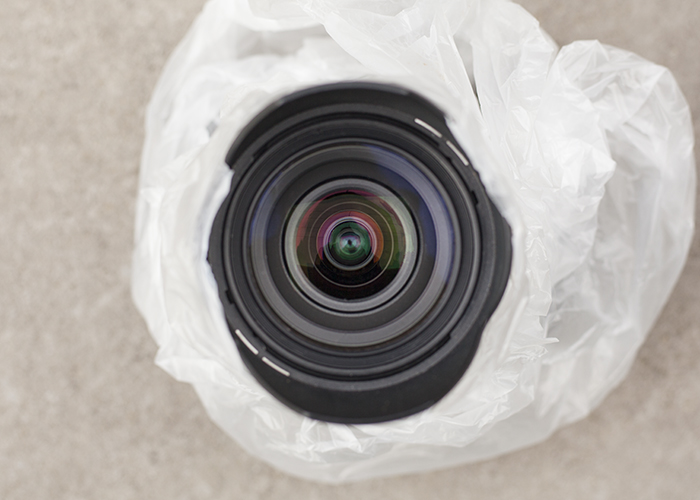 Overhead photo of a DSLR lens protected in plastic for rain photography
