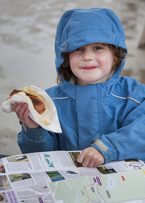 Portrait photography of a little girl in a blue rain jacket holding a sausage roll. Street photography tips