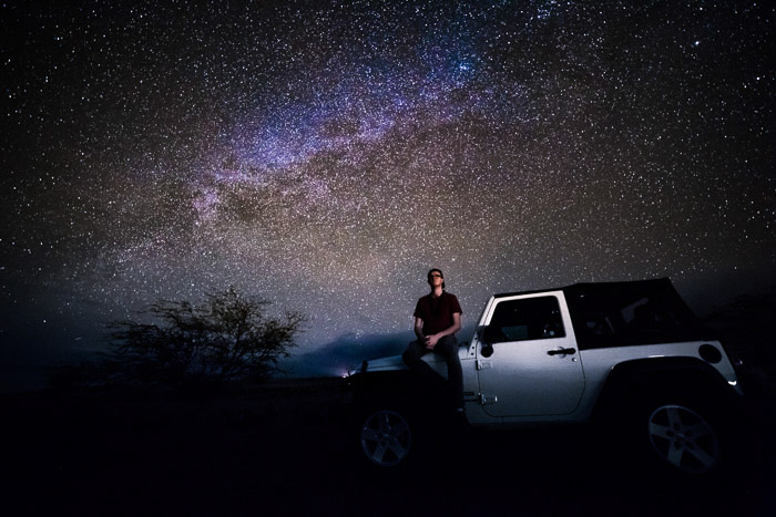 Full-Frame Astrophotography shot of a man sitting on a jeep with impressive star filled sky behind. Taken with rokinon 14mm lens at 30 Sec - F/2.8 - ISO 3200