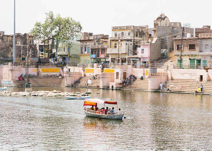 A boat on a river passing colourful buildings in India