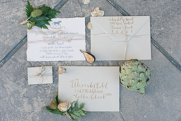 Personalized wedding invitations displayed on stone