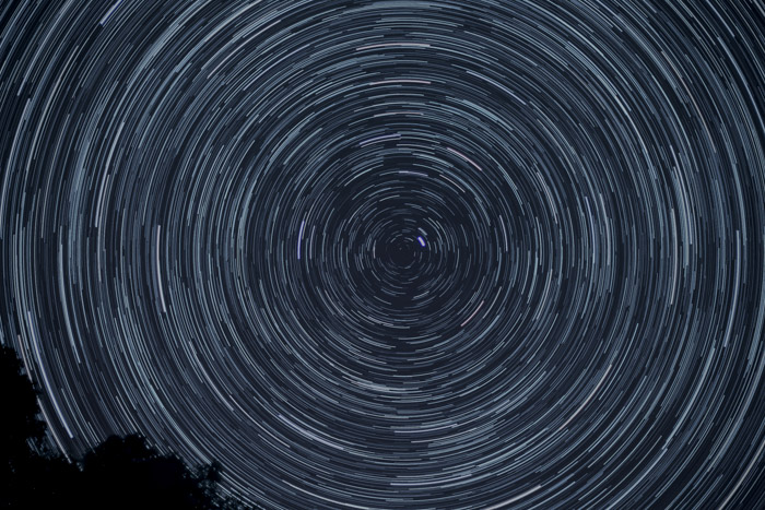 Long exposure night sky photography showing light trails in a circular pattern