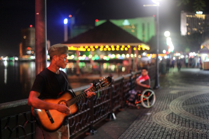 Street photography of a man playing guitar on a bridge at night using a 50mm f1.2L at f1.2 lens