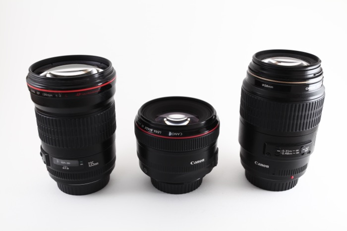 Image of 3 prime lenses on a white background