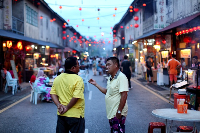 Documentary photography of two men chatting on a busy street using a 50mm lens, best lens for street photography