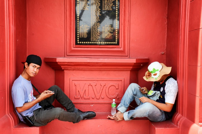Street photography of two people sitting on a red wall. Camera lens for street photography