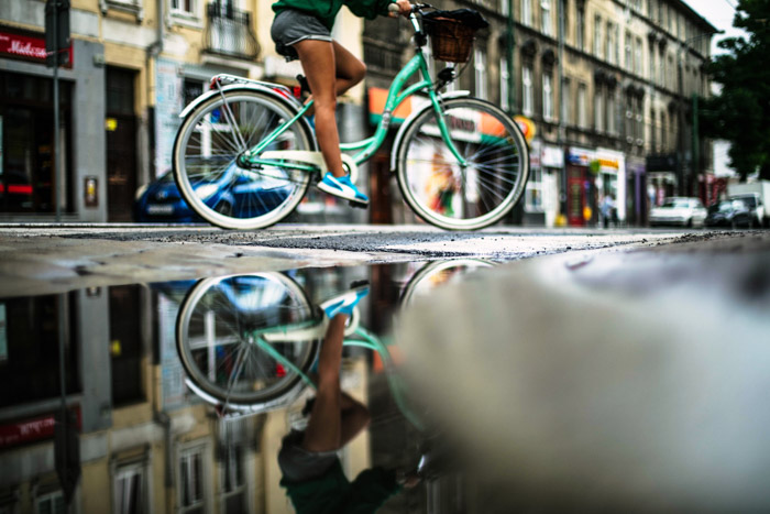 Photo of a person riding a bike through the streets taken from a low angle