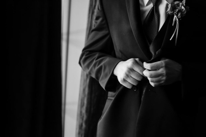 A close up black and white wedding photo of a groom buttoning his jacket. Wedding photography gear