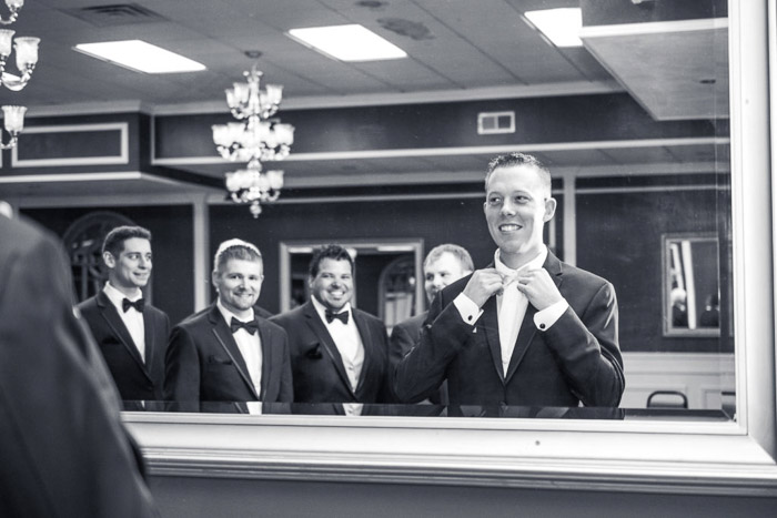 Black and white wedding photography a groom straightening his collar in a mirror