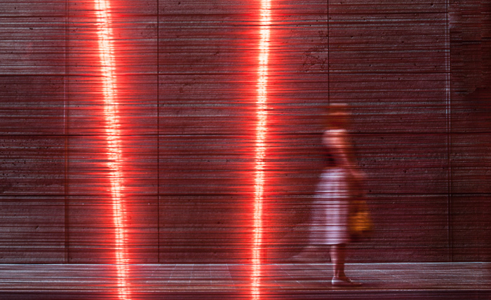 A color street photography shot of a woman walking past artwork 'Aeriology' by David Haines and Joyce Hinterding. black and white vs color street photography.