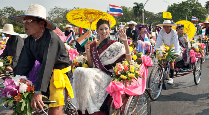An editorial photography shot of tricycle taxis in Chiang Mai carrying female Indian passengers in the annual Flower Festival parade.