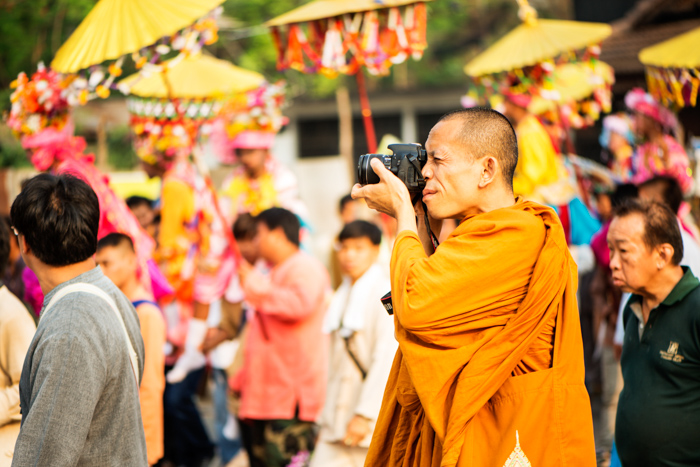 A Buddhist monk takes a photograph during the Poi Sang Long festival. This is an annual event when young boys who will enter the temple as novice monks are dressed in bright coloured costumes and make up and paraded around on the shoulders of male family members. Journalism or editorial photography.