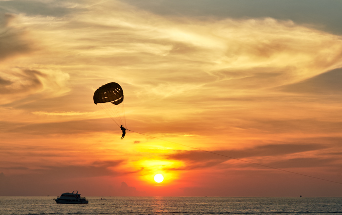 An editorial photography shot of someone parasailing over the ocean at sunset