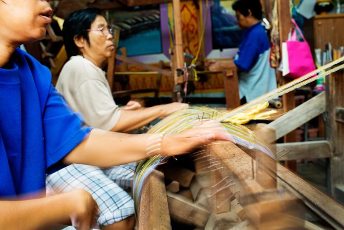 Women preparing silk thread for weaving in rural northern Thailand.