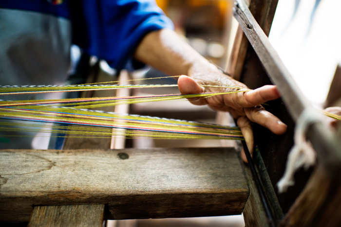 Macro editorial photography shot of a hand preparing the loom for weaving.