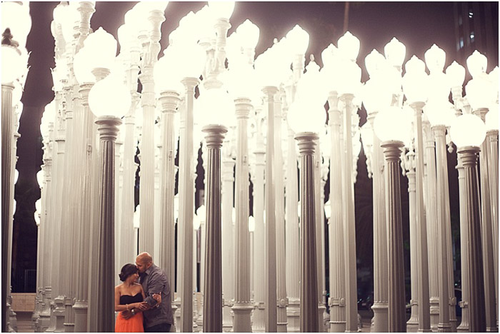 A romantic engagement photography shot of the couple in front of impressive lighted sculptures