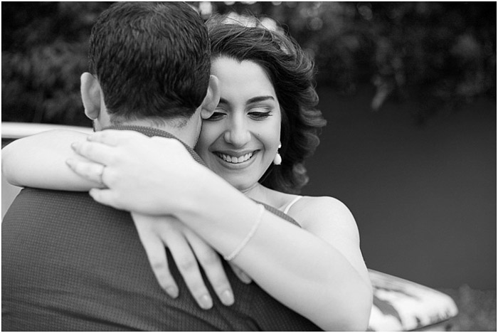 A black and white engagement photography shot of the couple embracing outdoors