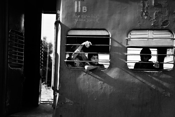 Black and white documentary photograph of boys looking out from a train window. Naturally framing photography.