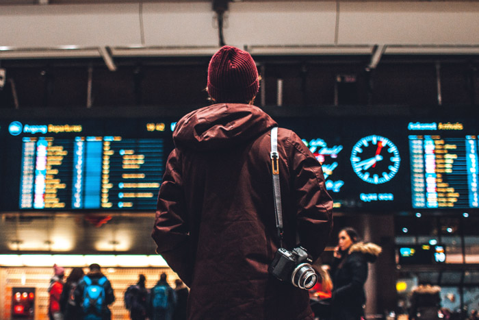 A travel photographer looking at the flight times at the airport - choosing great gifts for photographers who travel.