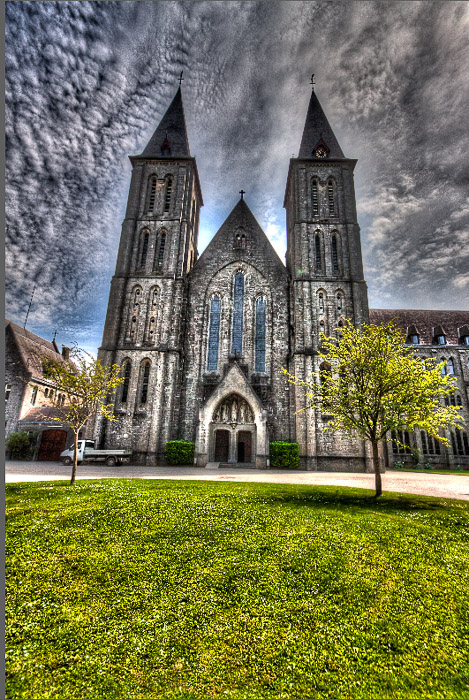 An over processed HDR photograph of Maredsous Abbey with black clouds, halos, and overcooked looks.