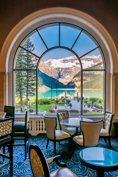 A stunning mountainous landscape shot through a large glass window with restaurant interior in the foreground - window how to make money with travel photography