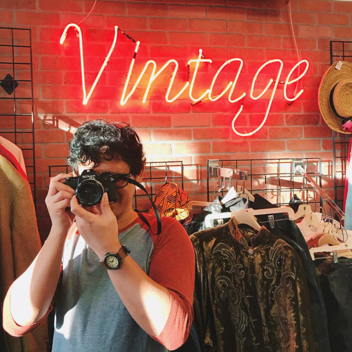 Portrait photography of a man in a vintage clothes shop holding a camera. Instagram tips for social media photography.