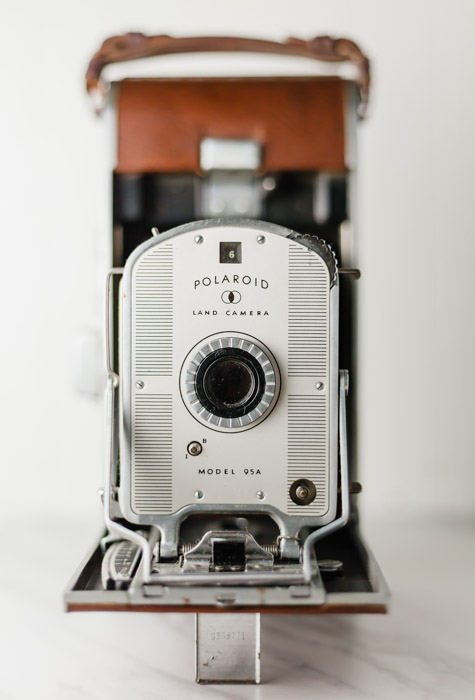 A portrait of the iconic polaroid camera on white background