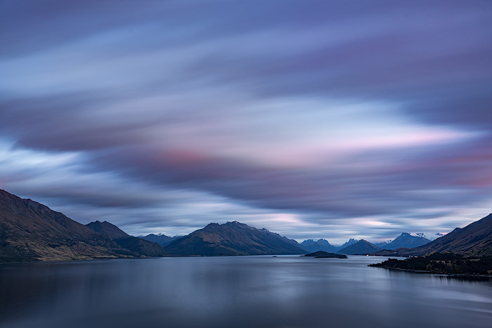 Long exposure landscape photo shoot showing fast moving clouds over mountains and water.