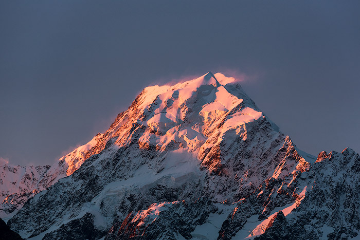Icy mountain peak photo shoot with pink light reflected on the snow