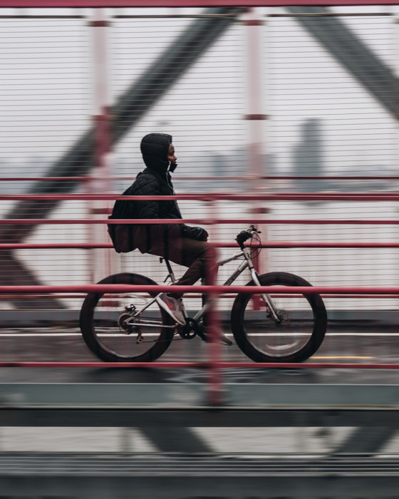 A movement shot of a person riding a bicycle across a bridge