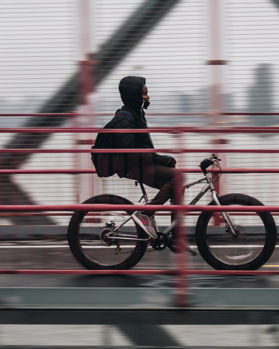 A cropped shot of a person riding a bicycle across a bridge