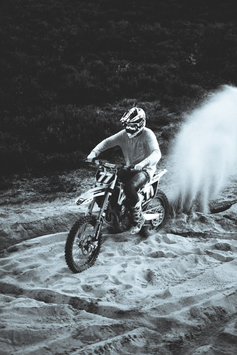 A black and white photo of a man on a bike going through the sand. He is very clearly the main focus of the photograph.
