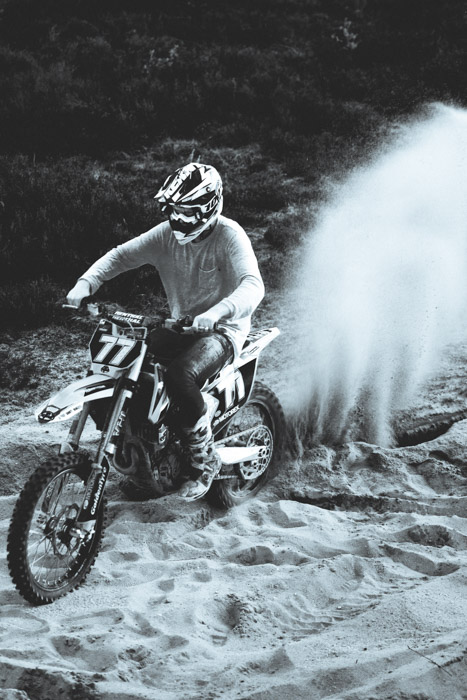 A cropped black and white photo of a man on a bike going through the sand.