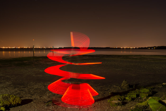 A red light paighting photography spiral on a beach at night.