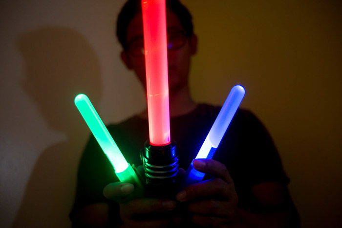 A man holding three coloured light sticks for light painting photography