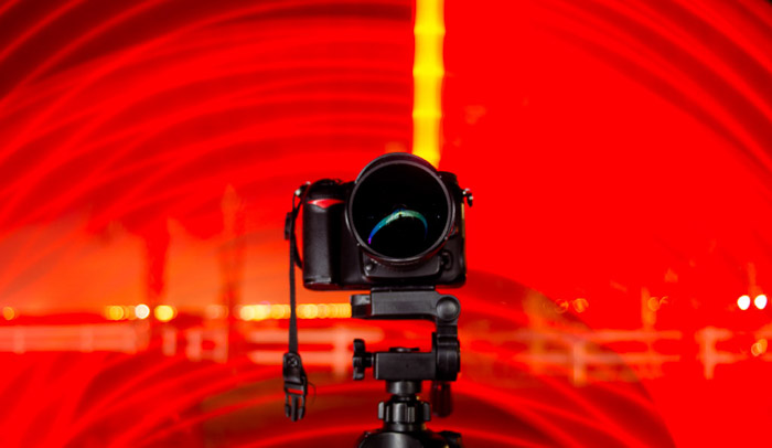 A DSLR camera on a tripod surrounded by a red light spiral.