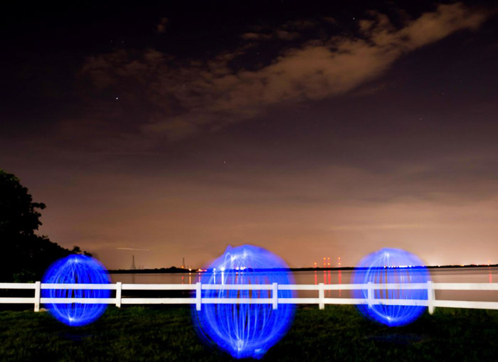 Three blue light painting orbs on a beach at night.