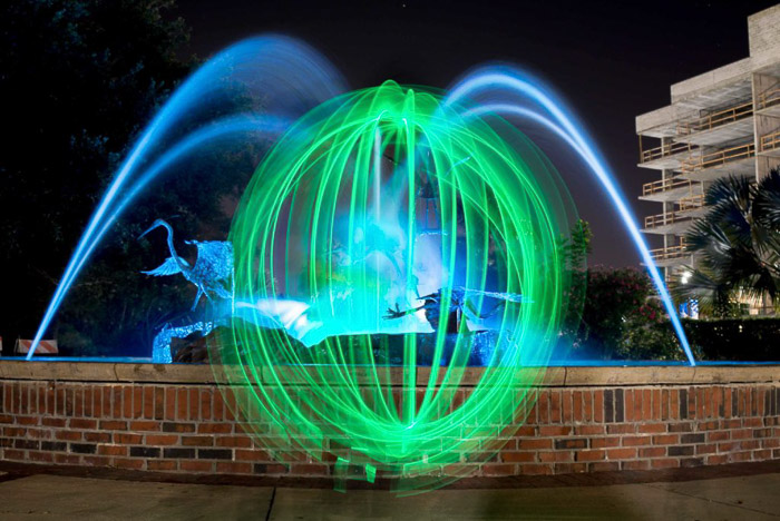 A green light orb in front of a fountain at night.