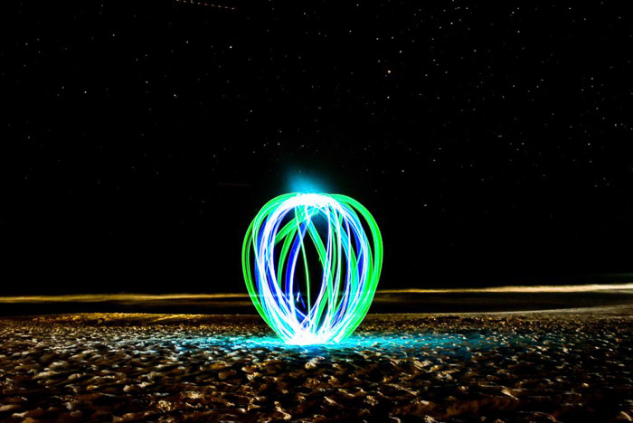 A green and blue light painting orb on a beach at night.